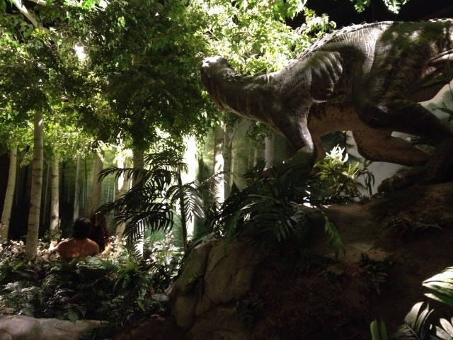 Adam and Eve overlooked by a dinosaur in the garden of eden.
